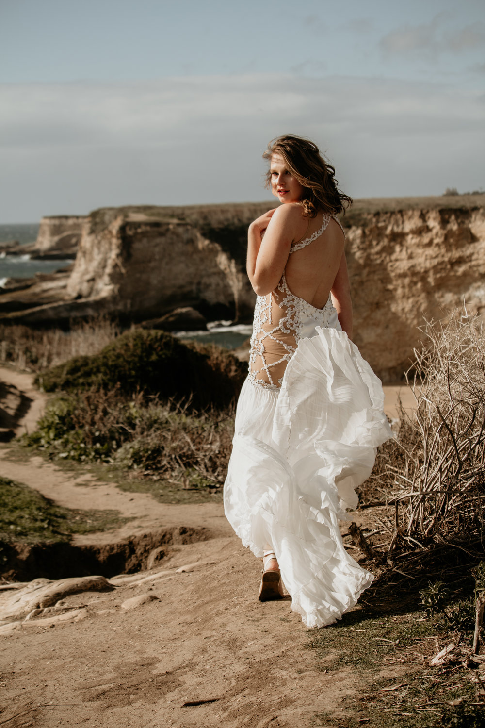 model at panther beach in santa cruz in lace and crystal bridal gown with windswept hair wearing soft natural romantic makeup by kim baker beauty san jose california makeup artist