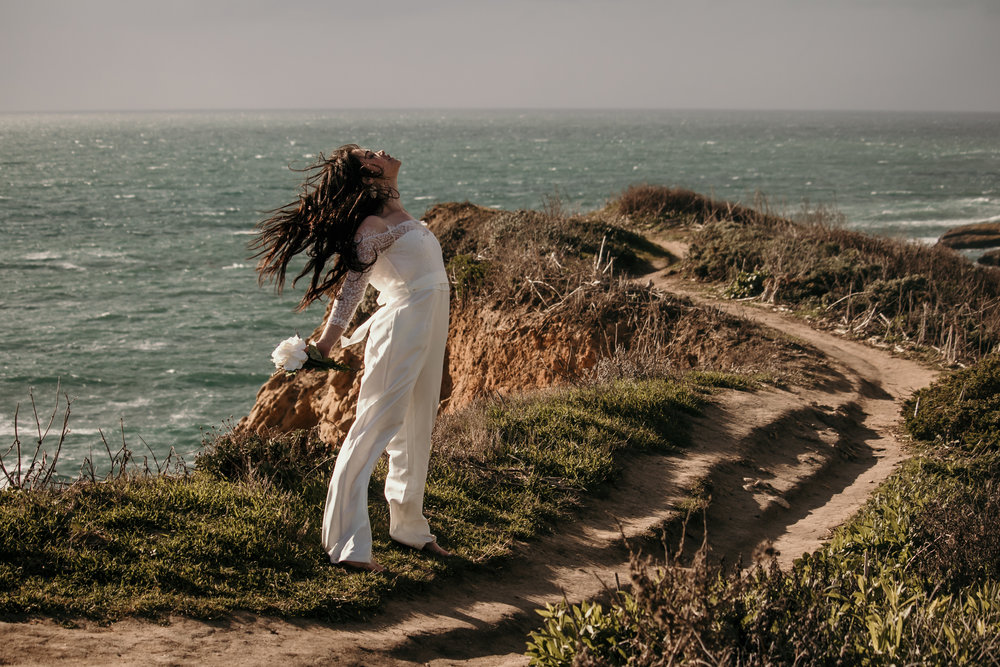 wind swept hair on model at panther beach in santa cruz in white lacey bridal jumpsuit and wearing soft romantic natural makeup by kim baker beauty san jose california makeup artist