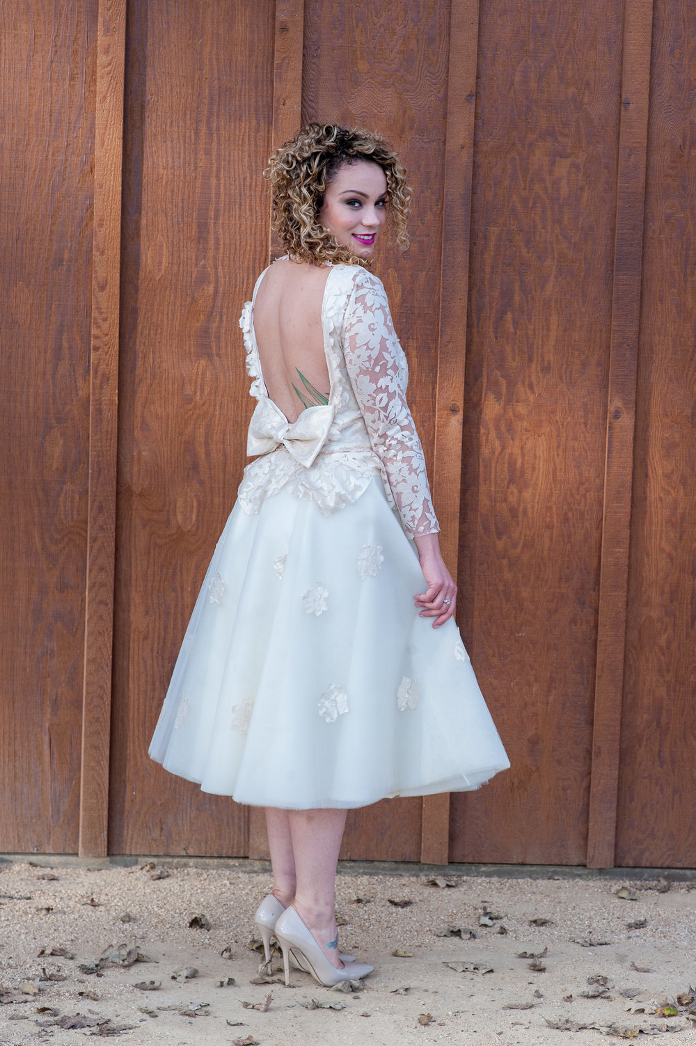 bride at engagement party in white lace dress by taste studio with curly side swept hair and bold pink lipstick and glowing soft glam makeup by kim baker beauty san jose california makeup artist