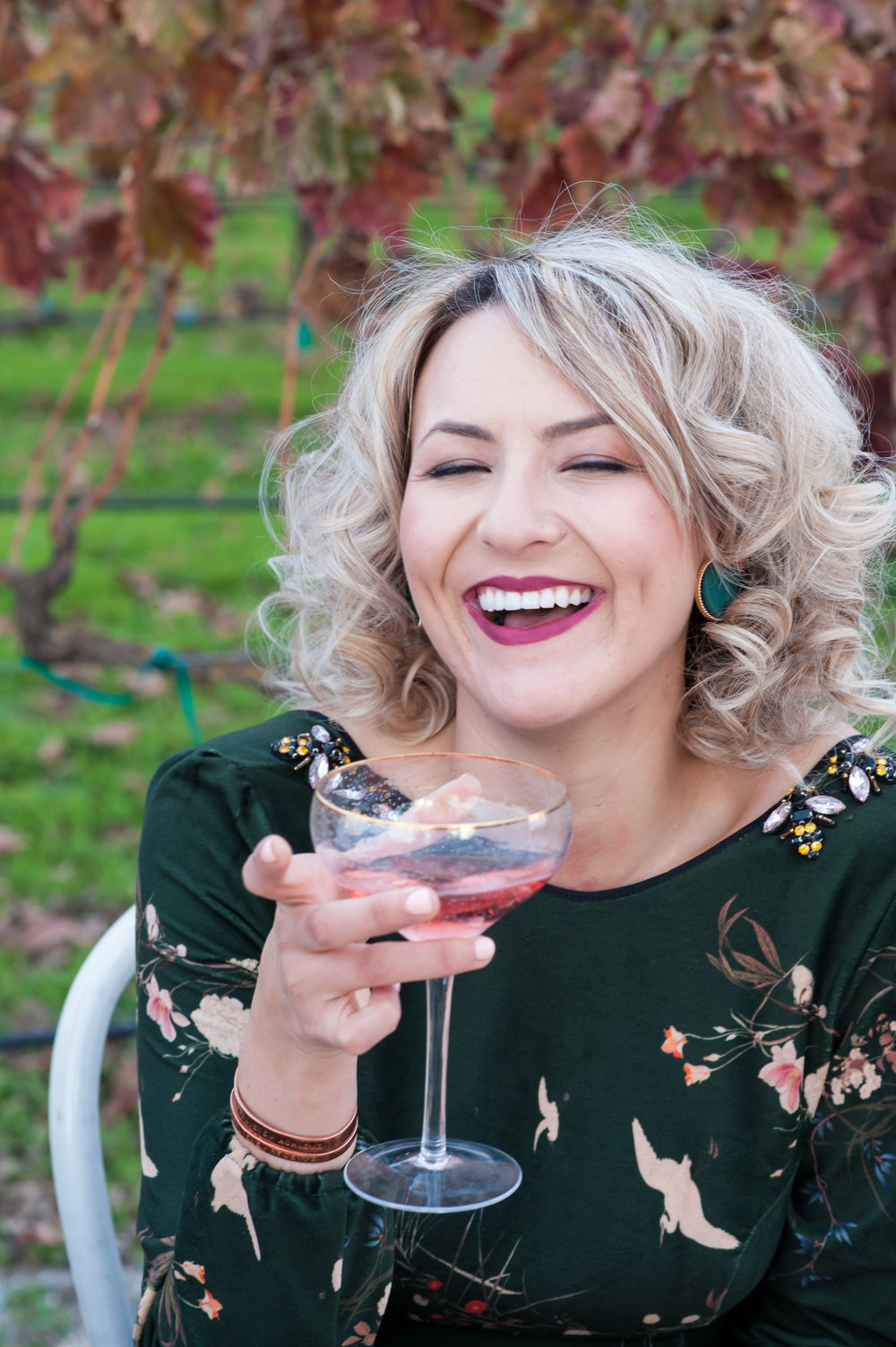 curly haired bridesmaid at engagement party cheersing to bride wearing hand made taste studio dress bold lipstick and soft glam makeup by kim baker beauty san jose california makeup artist