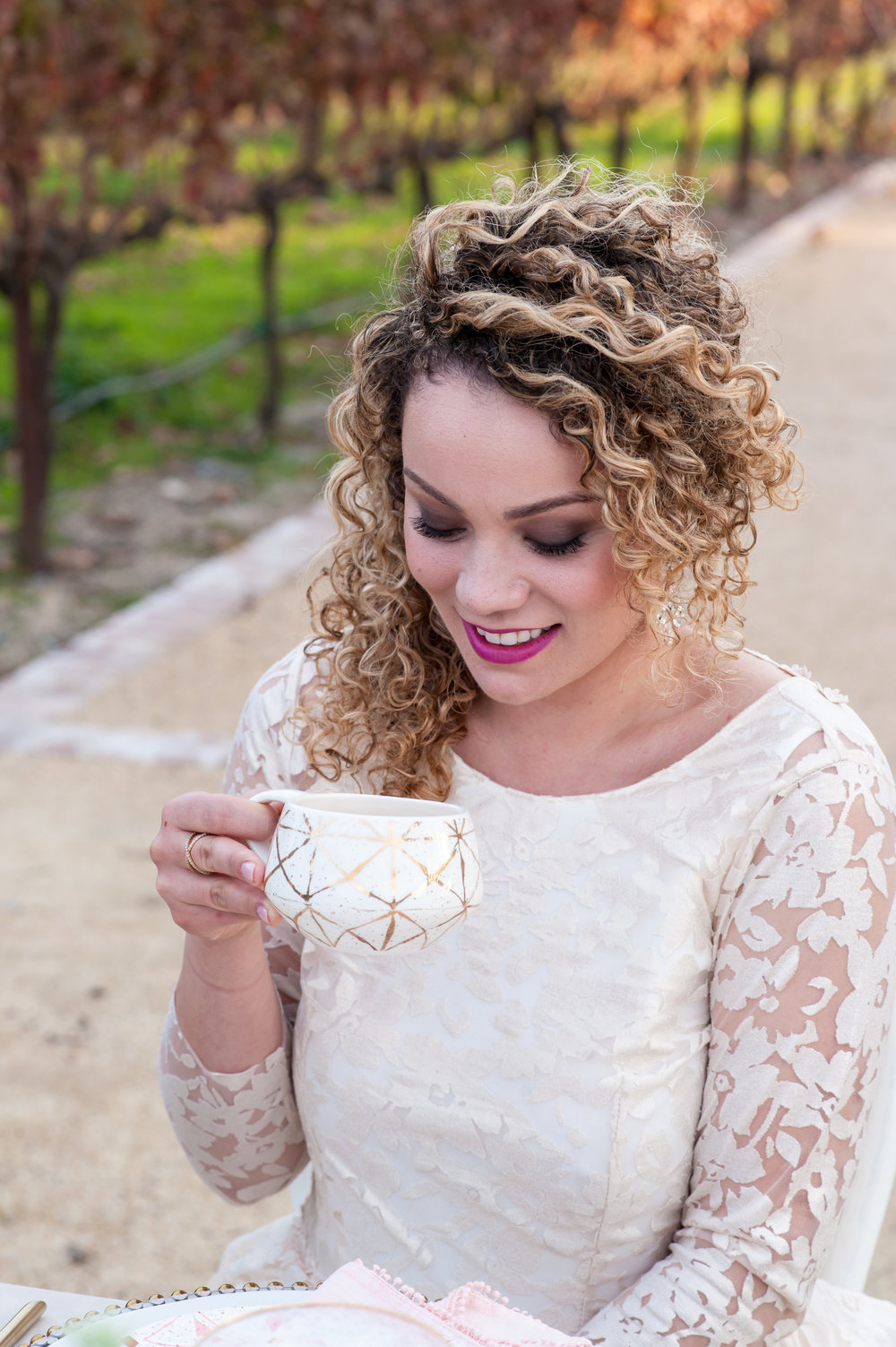 bride in white lace dress sipping tea wearing bold pink lipstick and soft romantic glam makeup by kim baker beauty san jose california makeup artist