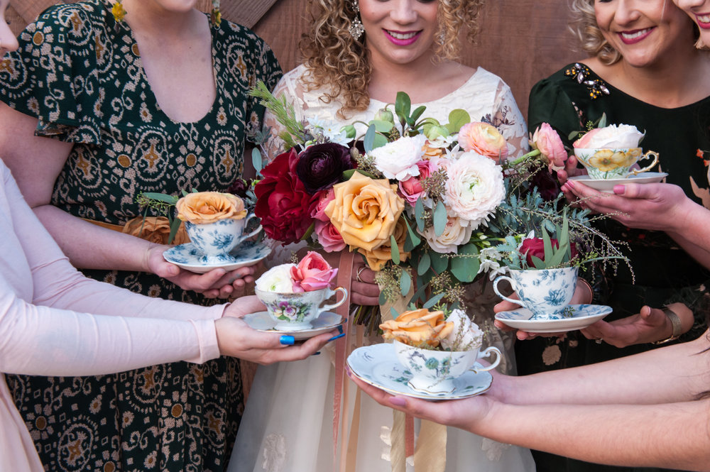 tea cups 2 candels with florals heald by models at the fitz place in san martin makeup by kim baker beauty san jose california makeup artist