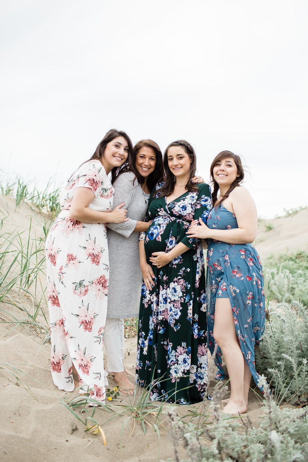 pregnant mom to be with aunts and grandma hugging on baker beach san francisco in floral print dresses rose toned romantic soft glam makeup by kim baker beauty san jose california makeup artist