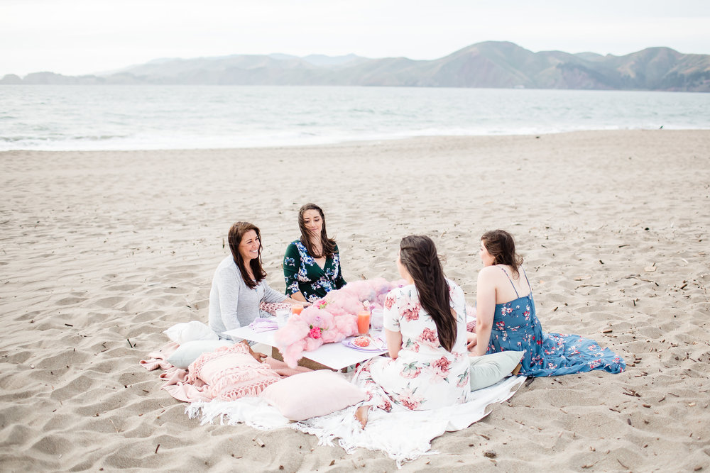 pregnant mom with aunts and grandma on baker beach san francisco with drinks and donuts wearing rose toned romantic soft glam makeup by kim baker beauty san jose california makeup artist