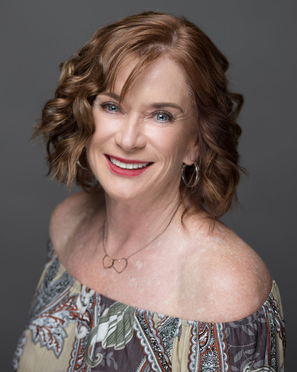 mature client smiling in off the shoulder top curled short hair soft red lipstick natural soft glam glowing makeup by kim baker beauty san jose california makeup artist