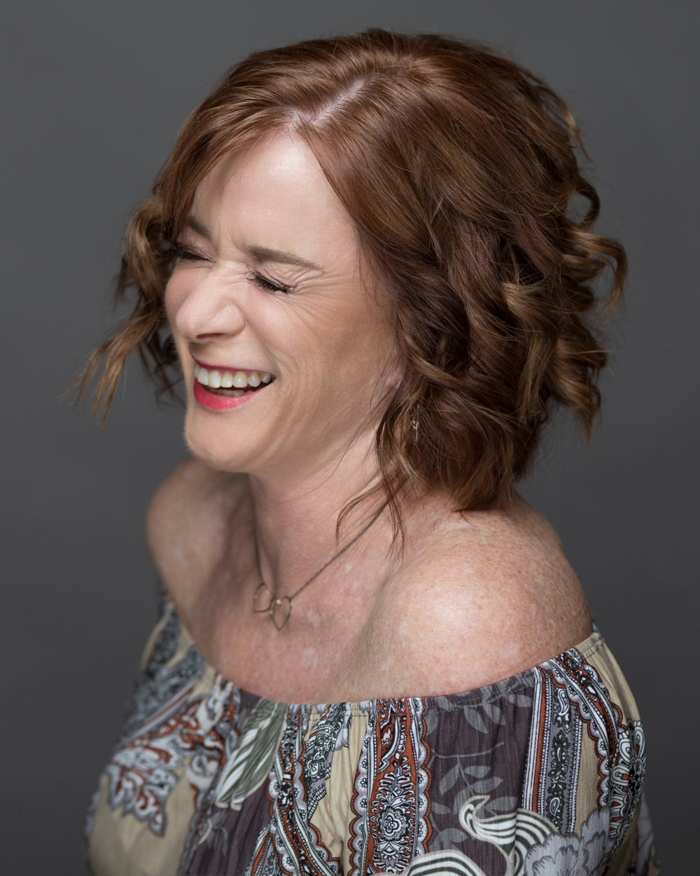 mature client laughing in off the shoulder top curled short hair soft red lipstick natural soft glam glowing makeup by kim baker beauty san jose california makeup artist