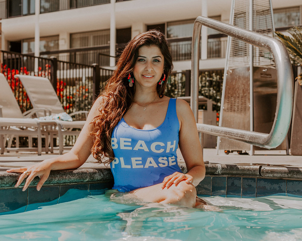 blogger raphael lobo in pool wearing blue one piece swimsuit beach please with long dark curls and skin forward glowing glamour makeup by kim baker beauty san jose california makeup artist