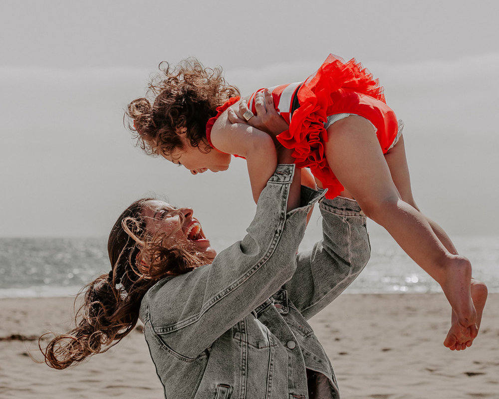 blogger raphael lobo and daughter playing at the beach windswept hair and soft glowing glam makeup by kim baker beauty san jose california makeup artist