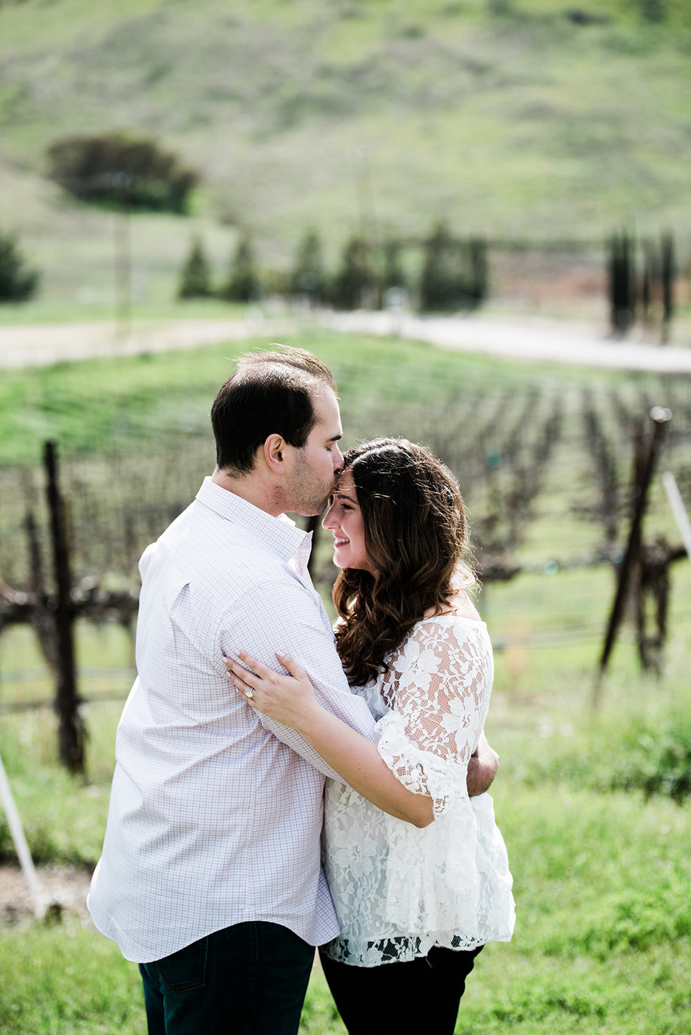 bride wearing lace off the shoulder top with curly hair and warm rose glowing makeup by kim baker beauty san jose california makeup artist and groom engagement photo session in livermore