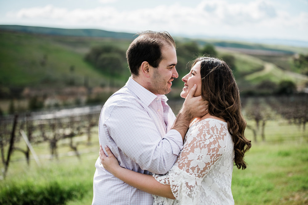 engagement photo session in livermore vineyards groom wearing button down and jeans with bride in white lace top and warm rose glowing makeup by kim baker beauty san jose california makeup artist