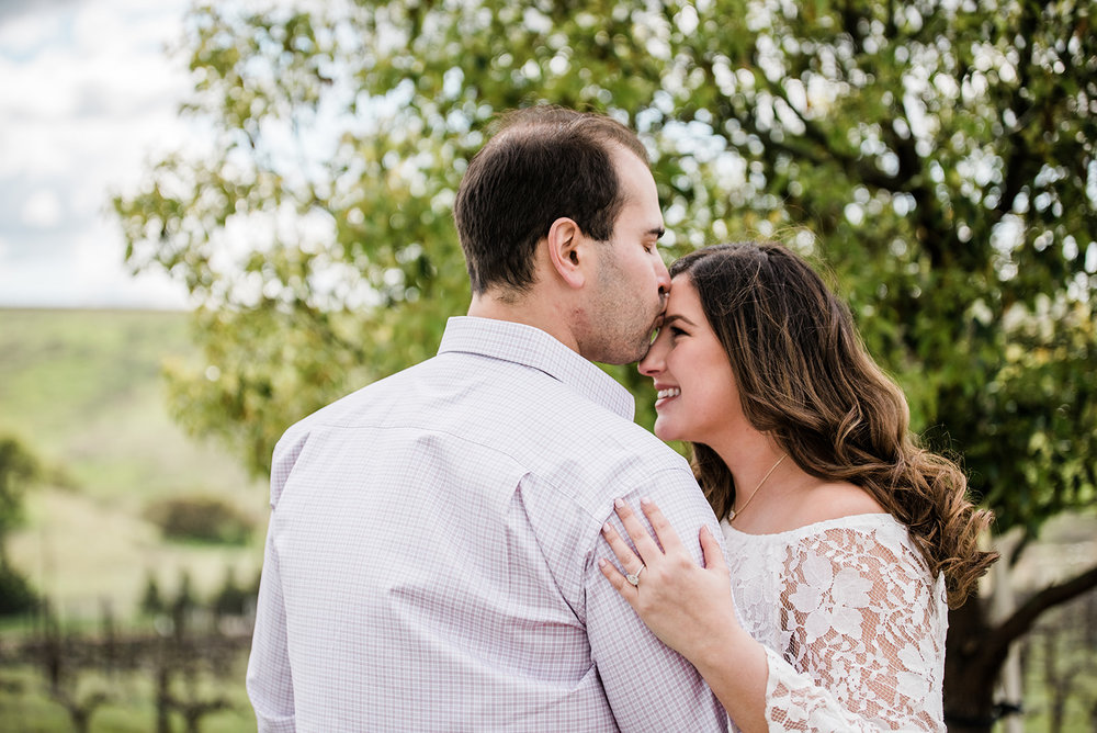 bride smiling at groom in livermore vineyard for engagement photo session with glowing dewey makeup by kim baker beauty san jose california makeup artist