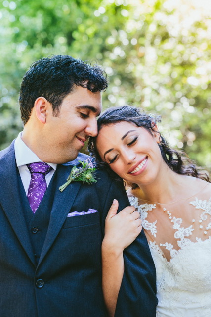 bride smiling and leaning on groom's shoulder in redwoods at pema osel ling in watsonville wearing natural glowing makeup by kim baker beauty san jose california makeup artist