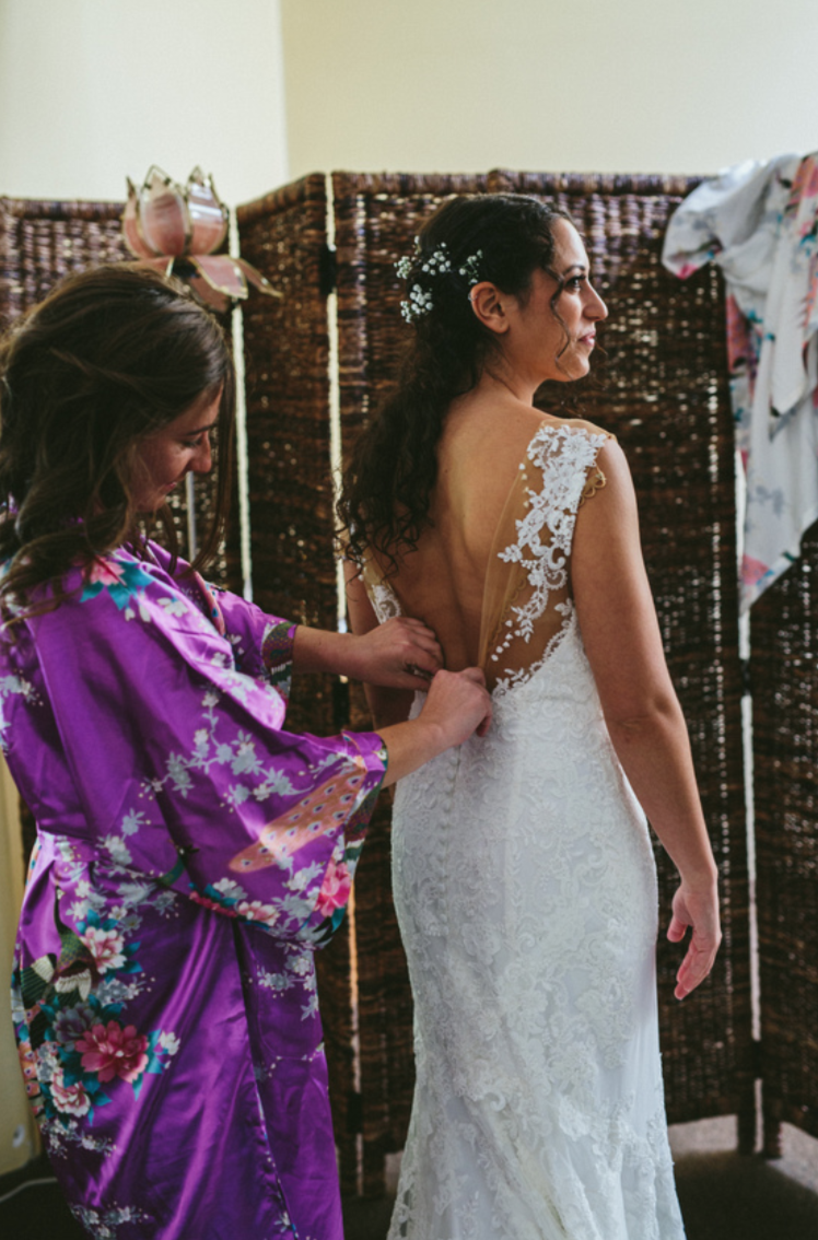 bridesmaid helping bride into lace button up floor length wedding gown at pema osel ling wedding in the redwoods kim baker beauty san jose california makeup artist applied natural glowing makeup