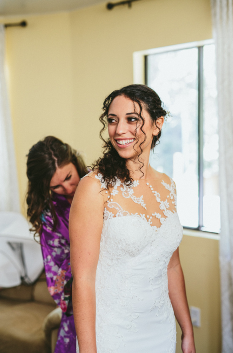 bride glowing while bridesmaid buttons up lace sweetheart wedding dress at pema osel ling wedding in the redwoods kim baker beauty san jose california makeup artist applied natural glowing makeup