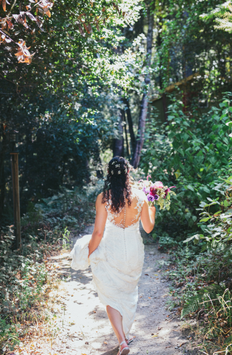 bride holding purple bouquet walking towards groom for first look in lace floor length wedding dress at pema osel ling wedding in the redwoods kim baker beauty san jose california makeup artist