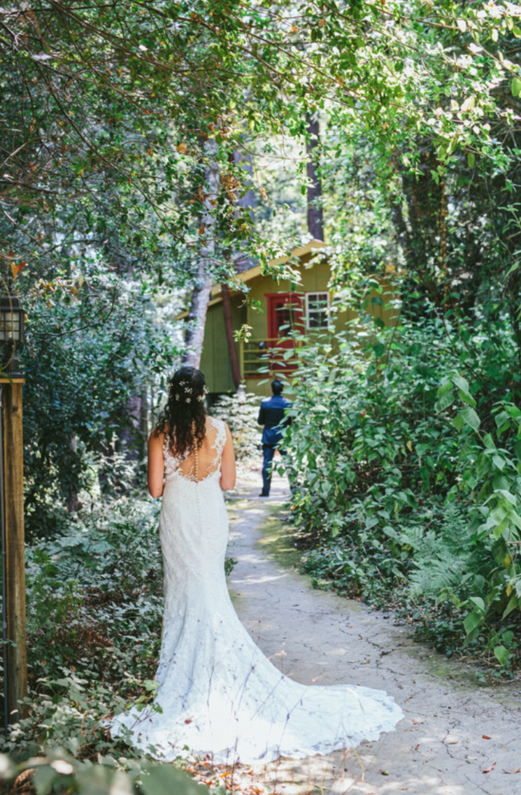 bride in the woods waiting for groom with lace floor length wedding dress with small train at pema osel ling wedding makeup by kim baker beauty san jose california makeup artist