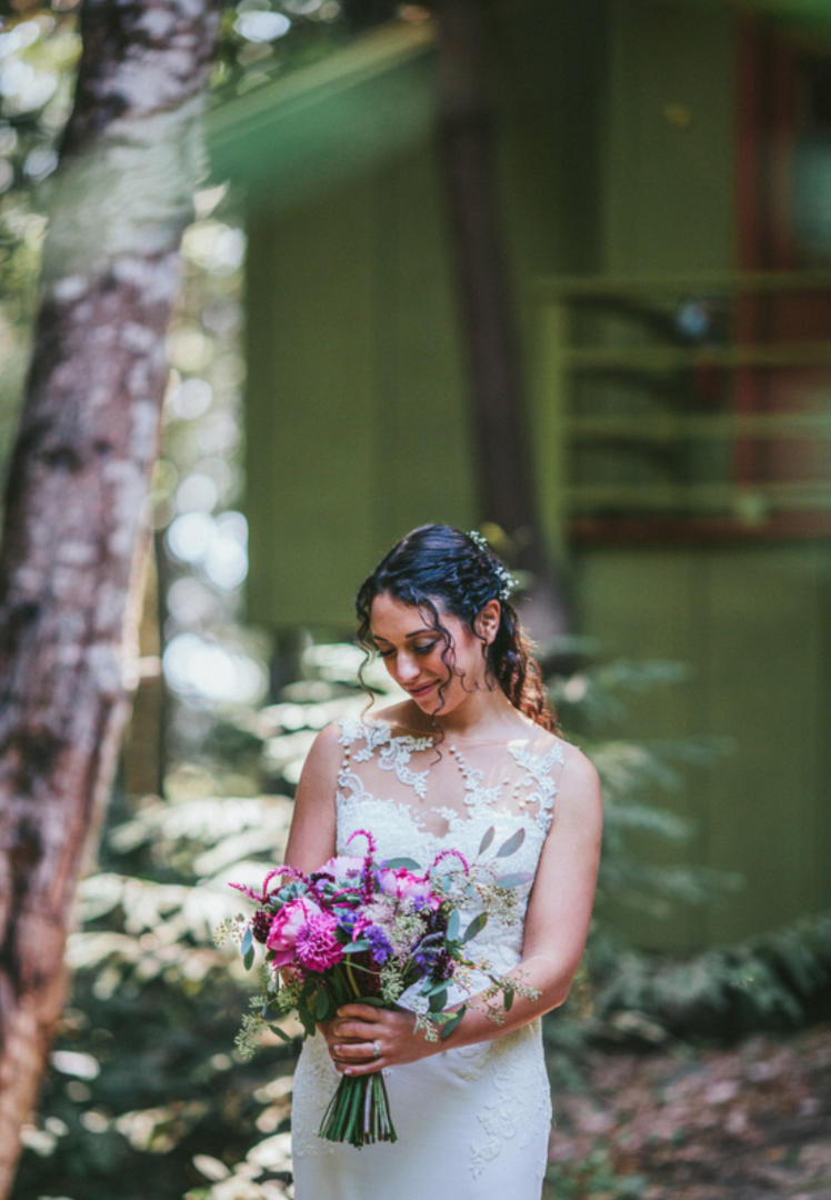 bride looking down and smiling at gorgeous purple floral bouquet on wedding day at pema osel ling wedding in the redwoods kim baker beauty san jose california makeup artist applied romantic makeup