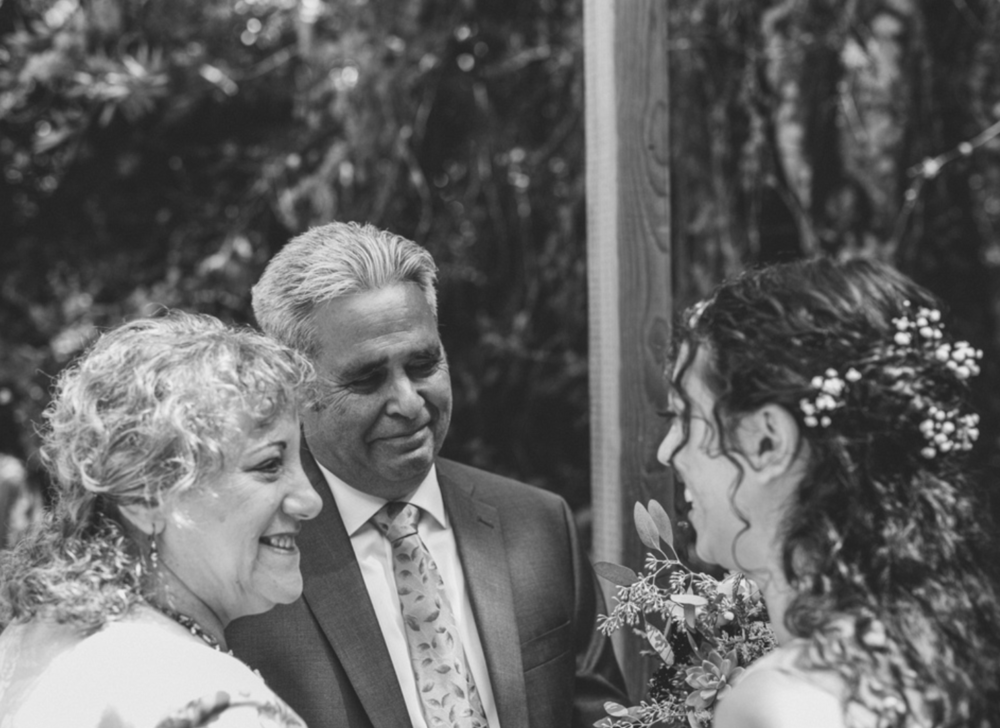 mother and father of the bride glowing with happiness at their daughter on her wedding day at pema osel ling redwood retreat in watsonville california