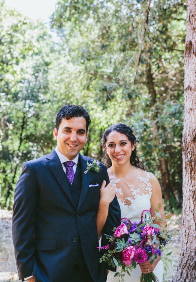bride wearing natural glowing makeup by kim baker beauty san jose california makeup artist while holding purple floral bouquet and grooms arm in redwoods at pema osel ling in watsonville