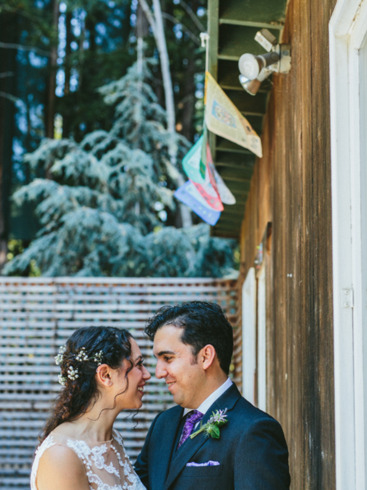 bride and groom smiling at one another against wood building at pema osel ling redwood retreat in watsonville romantic natural dewey bridal makeup by kim baker beauty san jose california makeup artist