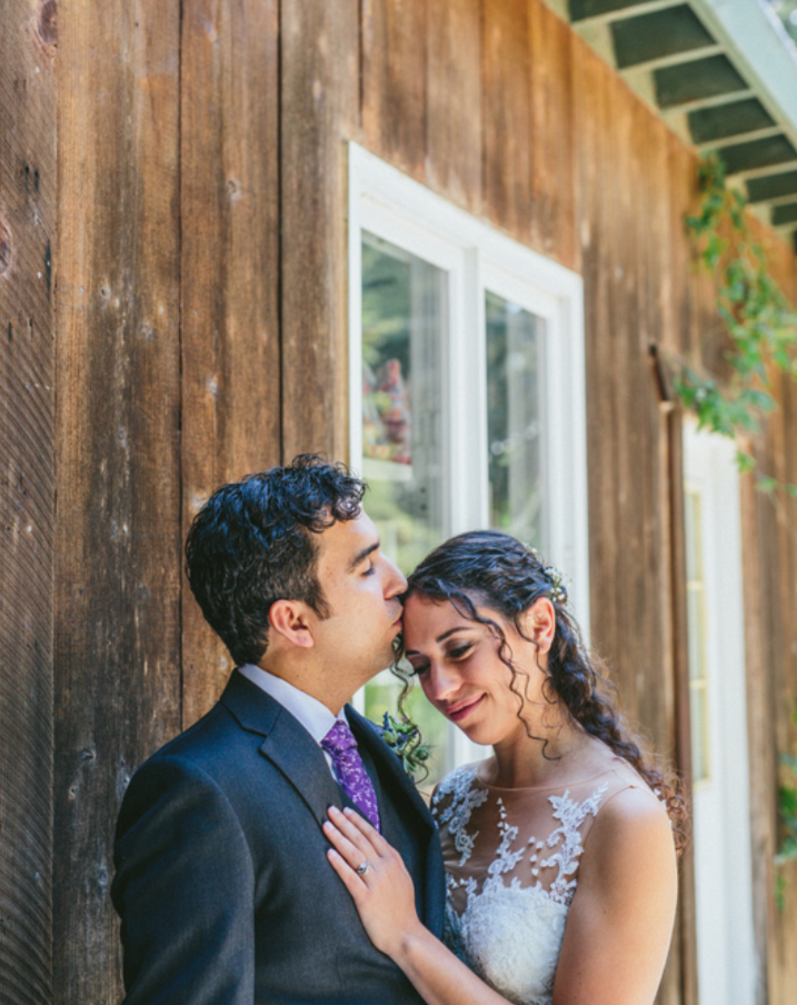 groom kissing bride's forehead at pema osel ling wedding in the redwoods kim baker beauty san jose california makeup artist applied natural dewey romantic makeup