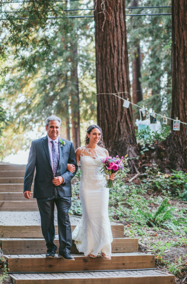 father of the bride walking his daughter down the isle at pema osel ling redwood retreat in watsonville soft romantic glowing dewey bridal makeup by kim baker beauty san jose california makeup artist