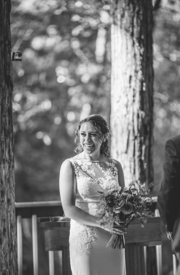 bride standing at the altar smiling at guests holding floral bouquet wearing lace sweetheart gown at pema osel ling in watsonville wearing makeup by kim baker beauty san jose california makeup artist