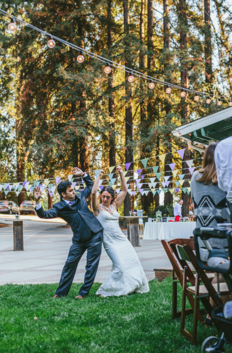 bride in white lace wedding dress dancing into reception with her groom after ceremony at pema osel ling redwood retreat in watsonvill santa cruz county california