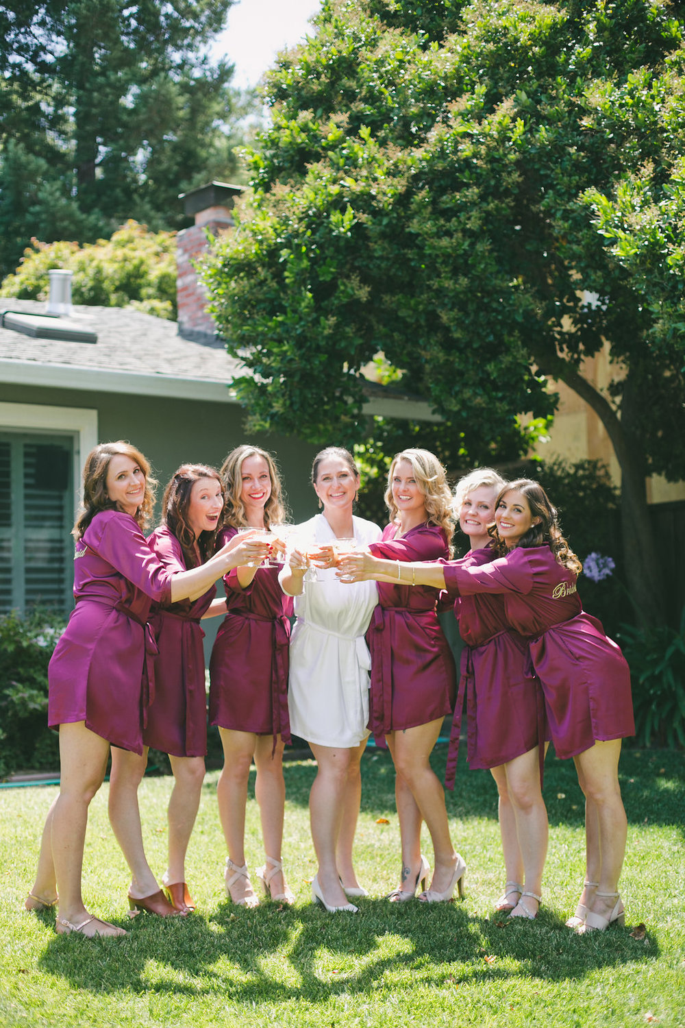 bridal party wearing maroon robes silk robes with bride in white cheering with champagne bride wearing glowing natural glamorous makeup by kim baker beauty san jose california makeup artist