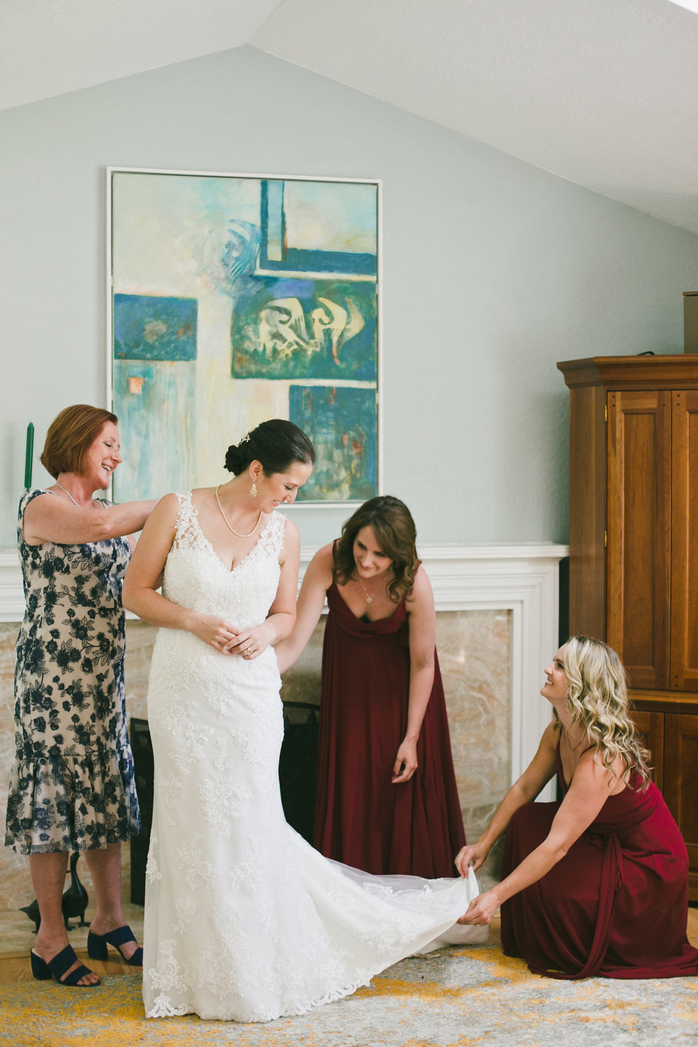 mother and bridesmaids in maroon floor length gowns help bride into her sleeveless lace dress wearing soft natural glowing glamorous makeup by kim baker beauty san jose california makeup artist