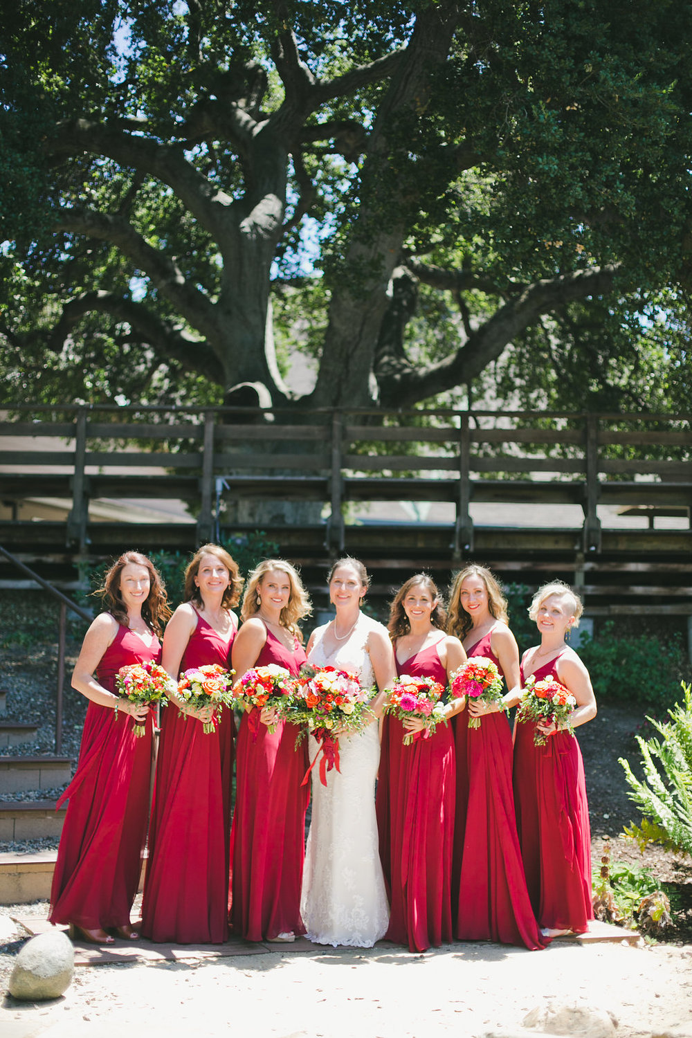 bridesmaids in deep red floor length gowns holding floral bouquets with bride in soft natural glamorous glowing makeup by kim baker beauty san jose california makeup artist