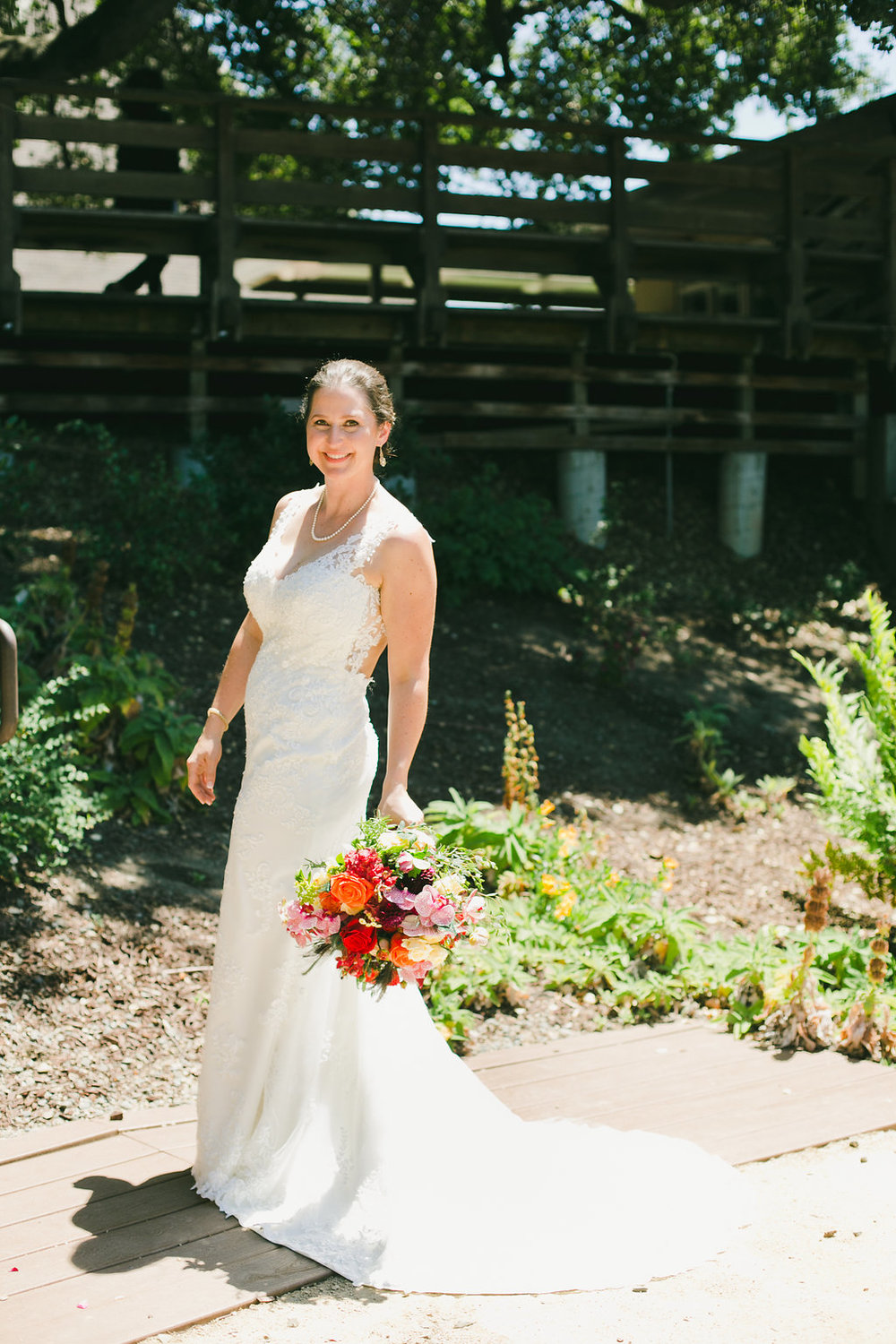 happy bride wearing a sleeveless lace gown holding her bouquet and wearing glowing soft natural glamorous makeup by kim baker beauty san jose california makeup artist