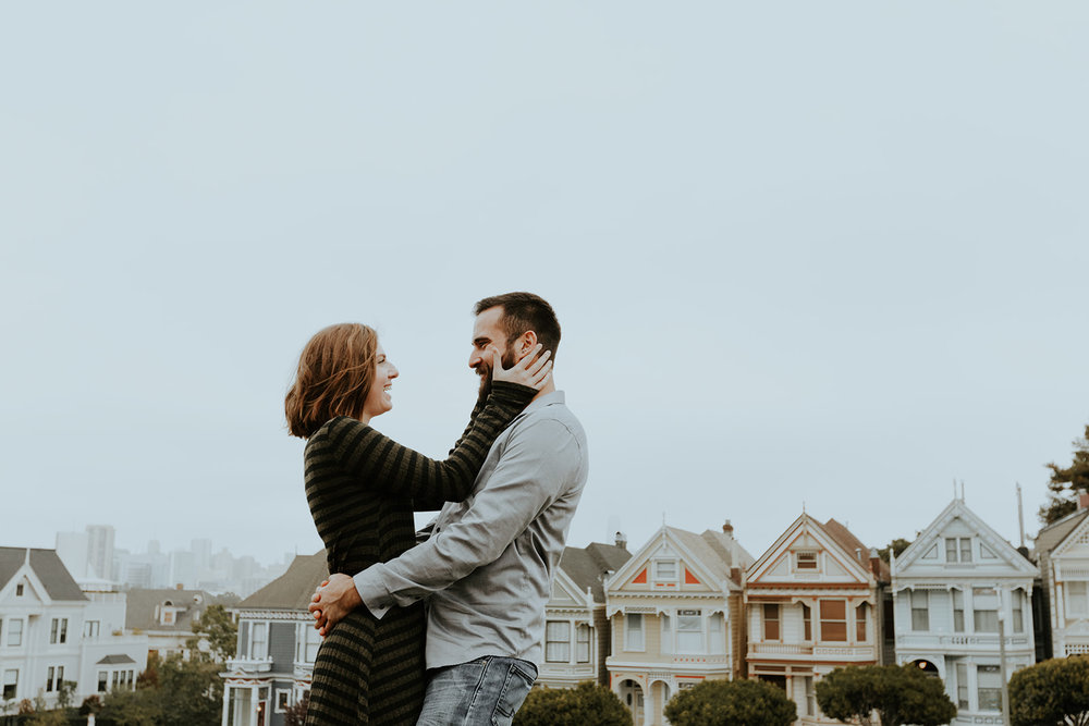 engaged couple in front of painted lady san francisco homes bride in subtle rose toned makeup by kim baker beauty san jose california makeup artist