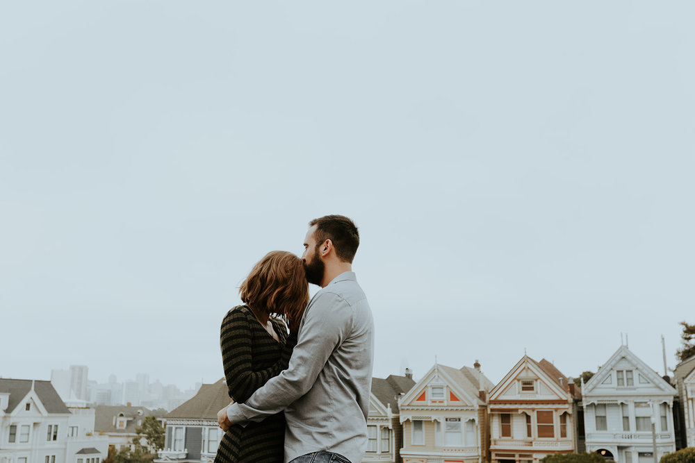 happy and in love engaged couple in front of painted lady san francisco homes bride in subtle rose toned makeup by kim baker beauty san jose california makeup artist