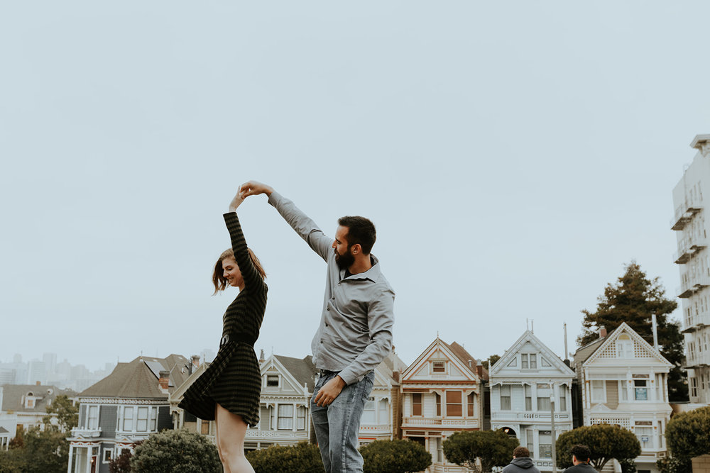 happy and in love engaged couple dancing in front of painted lady san francisco homes bride in subtle rose toned makeup by kim baker beauty san jose california makeup artist
