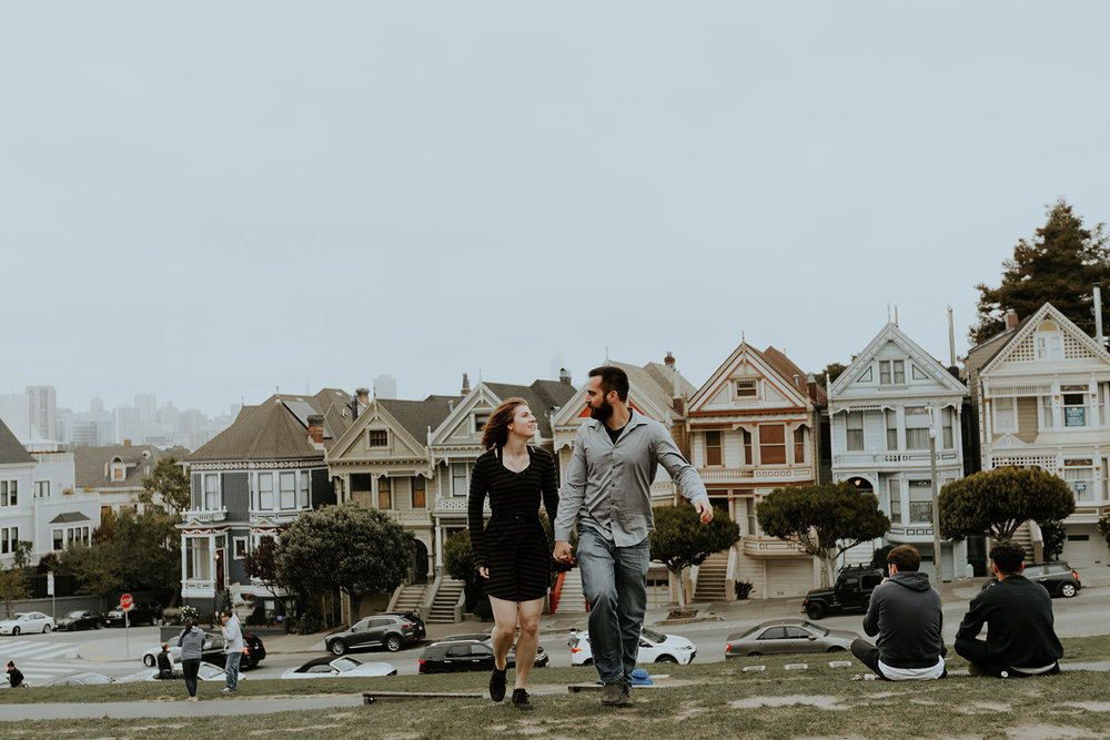 happy and in love engaged couple walking in front of painted lady san francisco homes bride in subtle rose toned makeup by kim baker beauty san jose california makeup artist