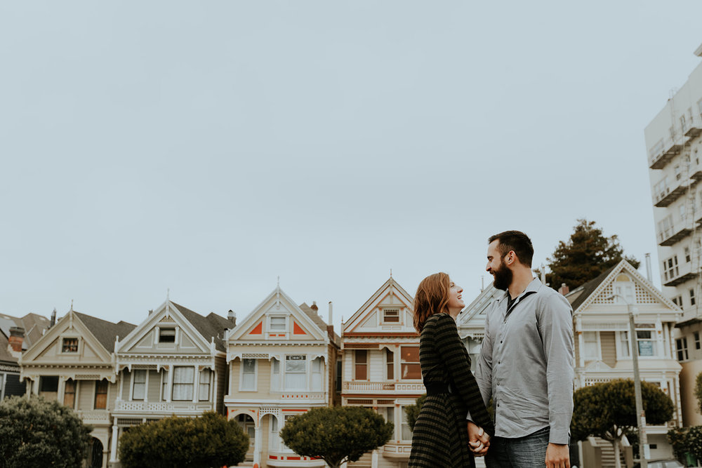 happy and in love engaged couple cuddling in front of painted lady san francisco homes bride in subtle rose toned makeup by kim baker beauty san jose california makeup artist