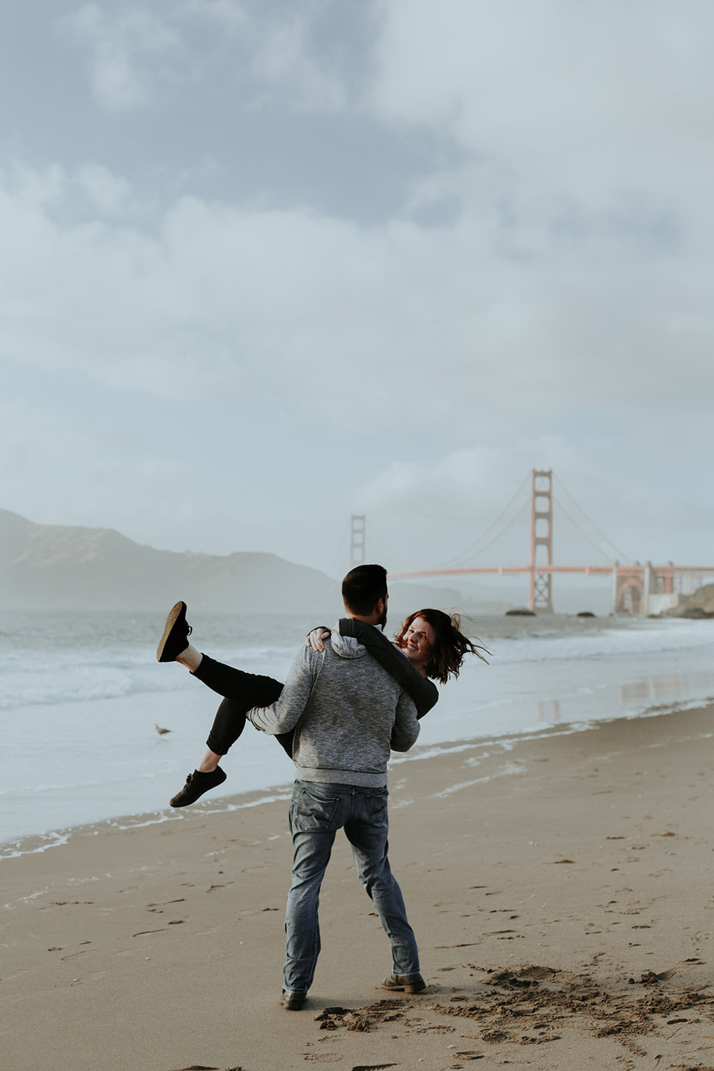 happy and in love engaged couple walking on baker beach in san francisco homes bride in subtle rose toned makeup by kim baker beauty san jose california makeup artist