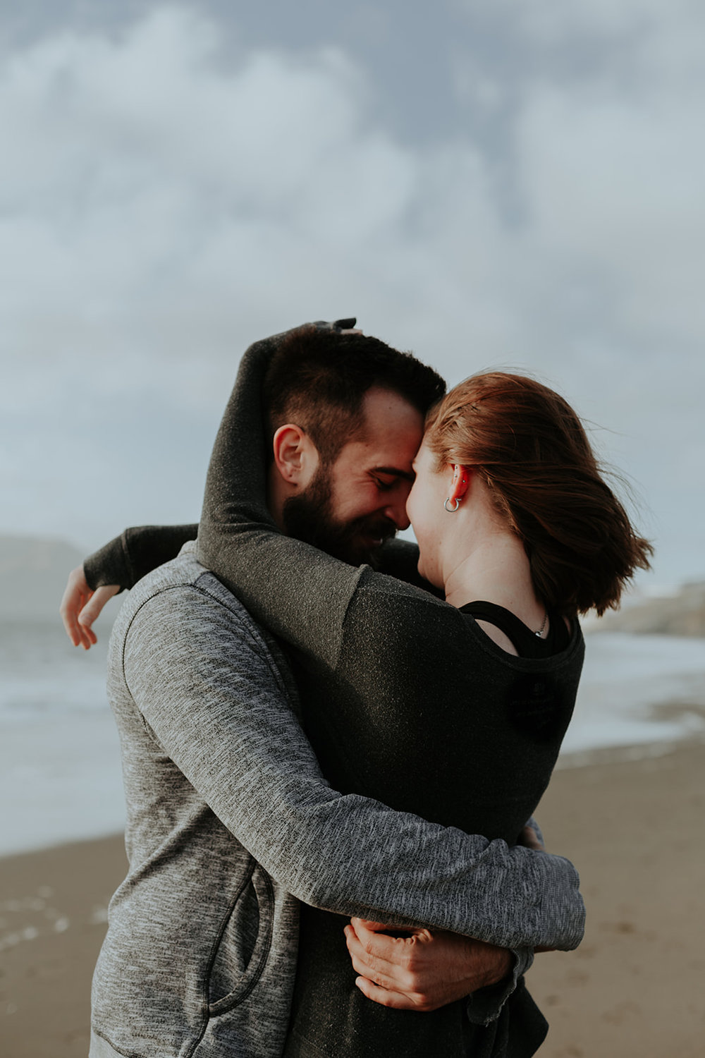 happy and in love engaged couple kissing on baker beach in san francisco homes bride in subtle rose toned makeup by kim baker beauty san jose california makeup artist