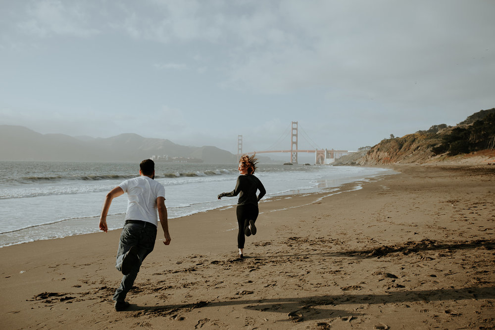 happy and in love engaged couple running on baker beach in san francisco homes bride in subtle rose toned makeup by kim baker beauty san jose california makeup artist