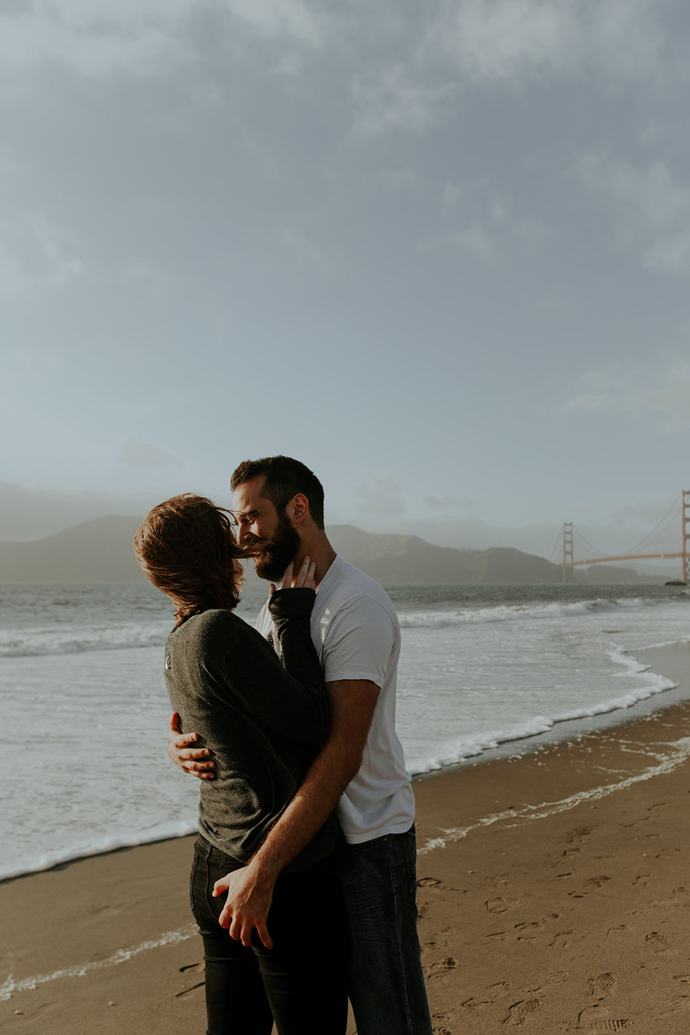 happy and in love engaged couple cuddling on baker beach in san francisco homes bride in subtle rose toned makeup by kim baker beauty san jose california makeup artist