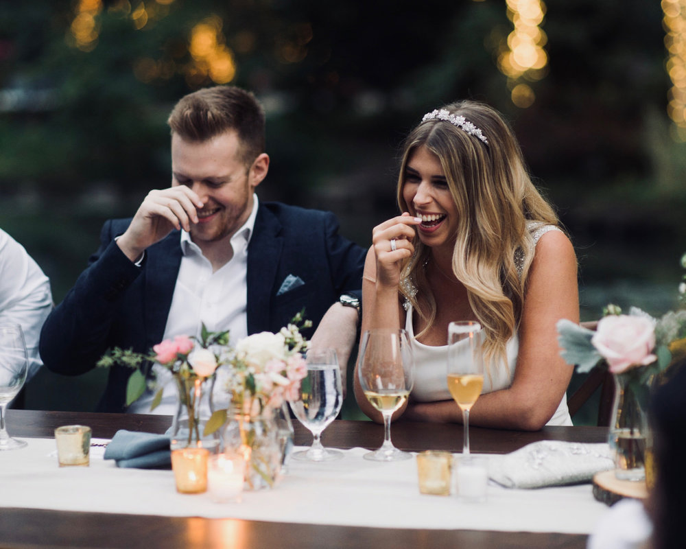 bride and groom happily laughing during dinner at nestledown wedding bride in veil and classic soft glowing makeup by kim baker beauty