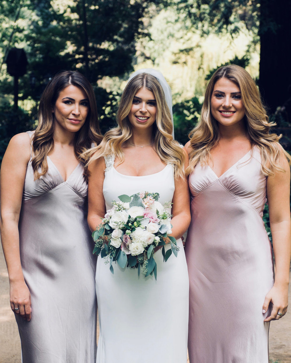 bride with bridesmaids in blush mauve silk floor length dress at nestledown los gatos wedding venue makeup by kim baker beauty