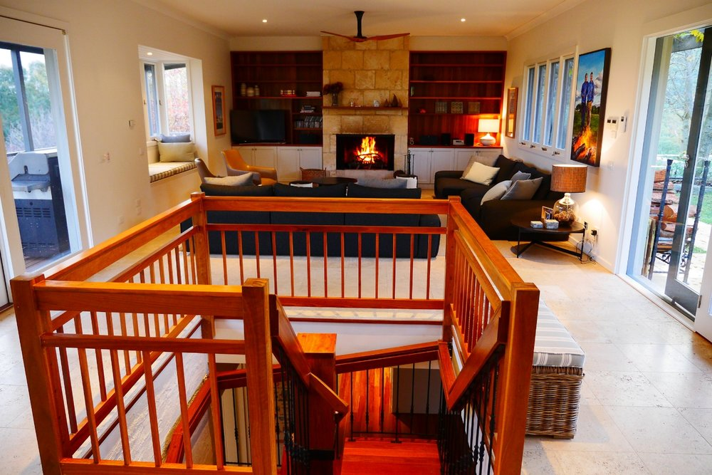 Main living space with open fire place, deck and access to pool and spa area.