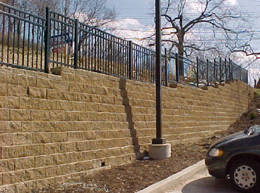 An aluminum fence along the top of this wall acts as a safety barrier to help prevent falls off the top.