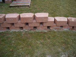 Wall batter - Many wall products have a built-in 'step back' in their design. The pictured stones have a 2-inch lip on the lower back edge to create the proper step back. With other wall stone you may need to create step back, or what is known as 'batter,' with the rule of thumb being a one-foot step back for every four-feet of wall height. This 'leans' the wall into the slope making it stronger.