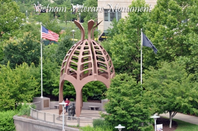 Vietnam Veterans Monument on Pittsburgh's North Shore.  The canopy covering the statues is taken from the shape of a hibiscus flower pod, an Asiatic symbol of rebirth and regeneration, symbolizing the warrior's return to peace to begin the journey of healing the scars of war.  On the ceiling of the canopy are wind chimes, signifying prayers for the dead each time they chime. The configuration of the statues is symbolic of the welcome home that veterans have historically treasured. The inscription in Vietnamese and English reflects the veteran's desire for peace - from war and within themselves. The monument is offered as a daily reminder that our veterans, living and dead, are not and will not be forgotten.
