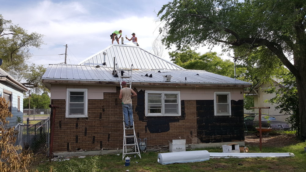 Interfaith volunteers work in SW Bricktown doing home repairs including a new roof.