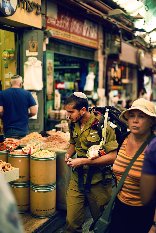 Soldier walking through the Mahane Yehuda Market.the Guild Magazine - Copyright 2018