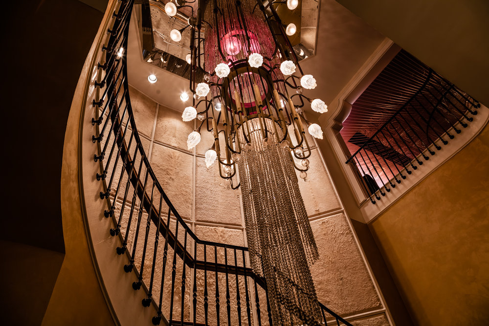 The circular staircase wraps around a two-story custom chandelier.